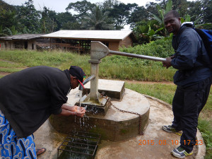 A photo of Dr. Richard Mbatu drawing water from a village well.