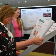 A photo of Regional Chancellor Dr. Sophia Wisniewska visiting with students and reading their research posters