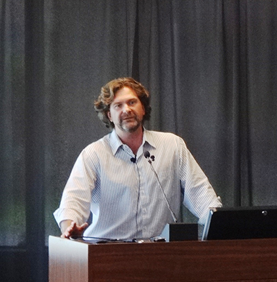 A photo of John Stanko, assistant professor of Graphic Design, presenting during the Faculty Lightning Talks event in 2015.