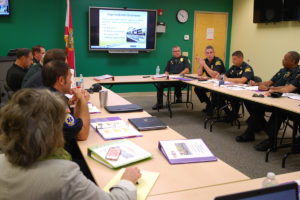 A photo of officials from USF St. Petersburg Police, St. Petersburg Police, and St. Petersburg Fire Rescue gathered around a table for a table time exercise and discussion