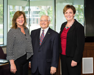 A photo of USFSP Regional Chancellor Sophia Wisniewska, Dr. Bill Heller, and WUSF General Manager JoAnn Urofsky standing side-by-side in the library.
