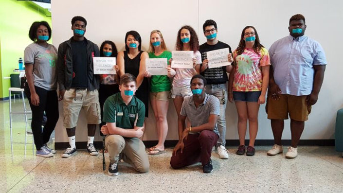 A group of USFSP students stand and kneel with tape over their mouths as part of the It's On Us campaign against sexual violence