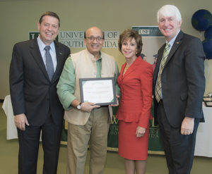 A photo of Dr. Hemant Merchant center, left, being recognized by Dr. Roger Brindley, USF System vice president, USF World; Dr. Judy Genshaft, president, USF System; and Dr. Ralph Wilcox, provost and executive vice president of Academic Affairs.