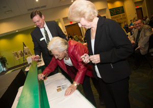 A photo of Ellen Cotton, Kate Tiedemann and Dr. Gary Patterson signing the beam as part of the