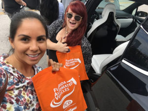 A photo of Ashley Huber and Lina Montoya at the Florida Automated Vehicle Summit with a Tesla model car