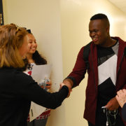 A photo of students with Holly Kickliter and Susan Toler shaking hands and speaking in Residence Hall One