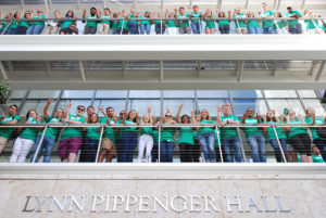 Students stand on the walkway at Lynn Pippenger Hall to watch the ribbon-cutting ceremony