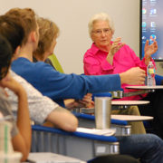 A photo of Kate Tiedemann sitting and speaking to a group of USFSP undergraduate students