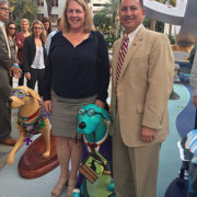 "A photo of Cathy Cardwell and Rick Kriseman standing on either side of the ""Duke"" dog sculpture"