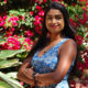 A photo of Deshanie Govender standing in front of backdrop of flowers and plants at USFSP