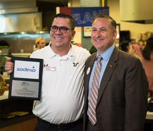 A photo of Louis Duran holding a plaque with Mayor Rick Kriseman
