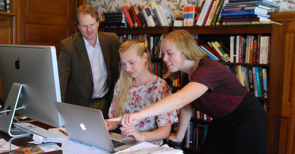 A photo of J. Michael Francis working with Rachel Sanderson and Hannah Tweet in his office