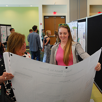 A photo of Regional Chancellor Sophia Wisniewska looking over a USFSP student's poster during the 2016 Student Research Symposium