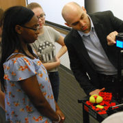 A photo of a faculty member showing students how to use the 3-D printer