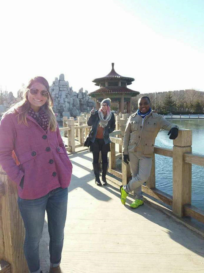 A photo of two women and a man standing by the waterfront in China