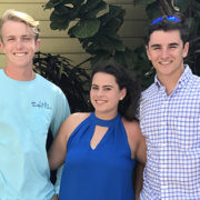A photo of Garret Greca, Savannah Billett, and Hunter Schoch standing side by side in front of a yellow building.