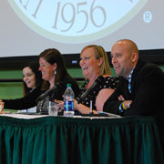 A photo of four panelists talking and laughing