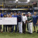 Group photo showing representatives from all organizations receiving 'Victories for Veterans' grants at Tropicana Field, including USFSP representatives Martin Tadlock and Milton White.