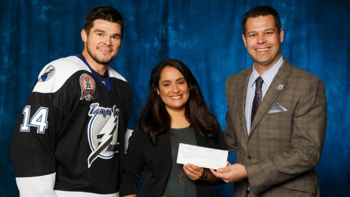 USFSP student Lis Casanova receiving a check from the Tampa Bay Lightning for her winning proposal to enhance an African American collection and create a multimedia innovation lab at the James Weldon Johnson Community Library in St. Petersburg.