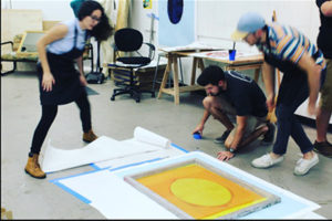 Students working on a new print that will hang outside the University Student Center Ballroom.