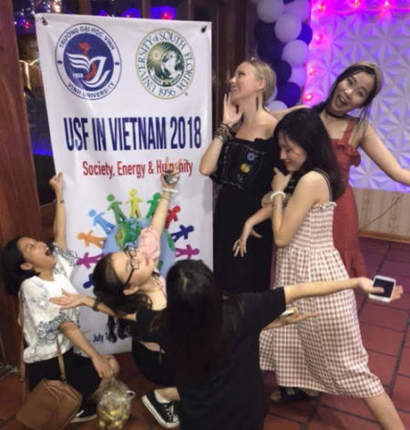 Emma Roberson, standing center, and Minh Anh Nguyen, back right, take part in the opening ceremony for the education abroad program in Vietnam. During the ceremony, students bonded at a nice restaurant, sang Karoke, danced and took pictures in front of the program sign.