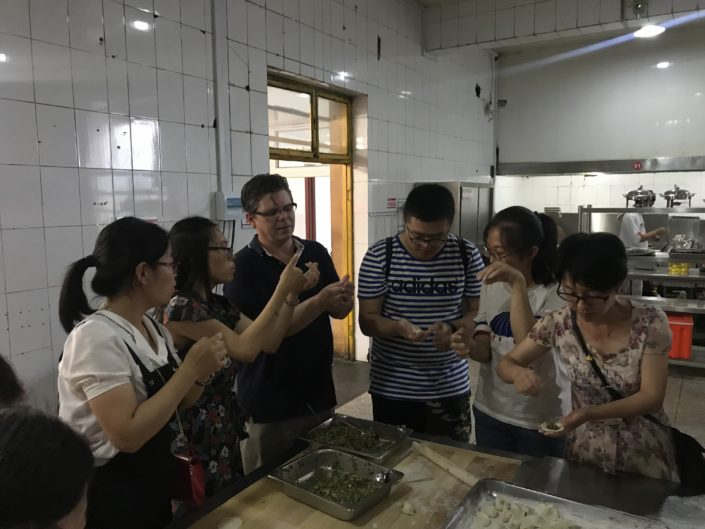 Chemistry Instructor John Osegovic not only taught students, but was taught by them, here learning how to make dumplings.