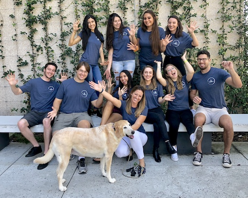 Professor Lindsay Rodriguez (front, center) with students who work in her lab and her dog.