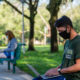 students wearing face masks sitting on benches on campus